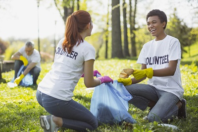 volunteers holding garbage bag and communicating